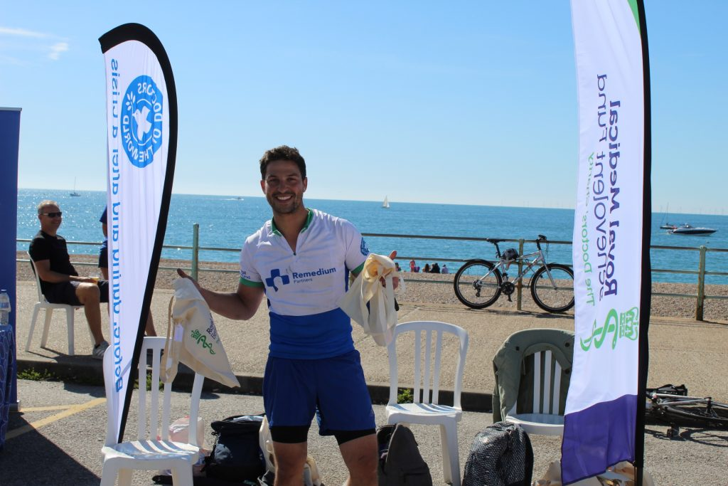 Cyclist Oliver Jansen smiling and holding a goodie bag in the sun on Brighton seafront
