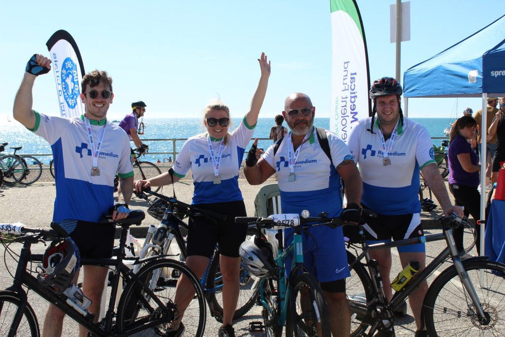 Four cyclists from Remedium Partners posing with their bikes on Brighton Seafront