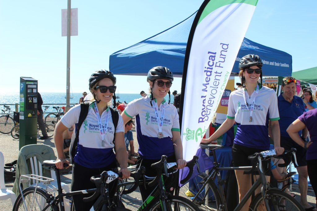 Three cyclists, Elizabeth Nally, Sarah Hancox, and Lizzie Kostev, standing with their bikes in the sun at the Brighton seafront, wearing RMBF cycling tops